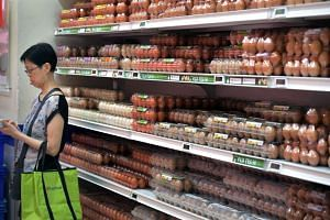 A shopper standing next to the eggs section in the NTUC Fairprice outlet at Toa Payoh HDB Hub.