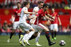 Manchester United's Henrikh Mkhitaryan (in red) tussling for the ball with Swansea's Top Carroll (left) and Gylfi Sigurdsson during their EPL match on April 30, 2017.
