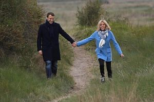 French presidential election candidate Emmanuel Macron and his wife Brigitte Trogneux pose for photos in Le Touquet, northern France on April 22, 2017.