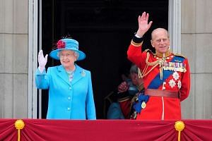 Britain's Queen Elizabeth and Prince Philip wave from the balcony of Buckingham Palace after attending the Trooping the Colour ceremony in London in this June 13, 2009 file photo.