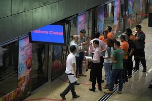 SBS Transit staff at the faulty platform doors at Botanic Gardens MRT station along the Downtown Line yesterday. The affected doors at the station did not open automatically and had to be operated manually each time a train pulled in, causing dela