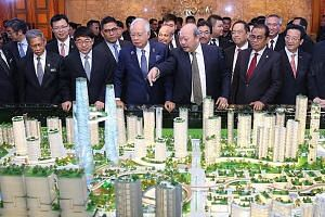 Tan Sri Lim Kang Hoo pointing out features on a model of Bandar Malaysia to Prime Minister Najib Razak last year. Unlike that project, many other deals with China have not even seen binding legal agreements, among them the Melaka Gateway port.