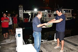 Boat captain Ricky Tan (right) performing a ritual to wash away bad luck with the help of his friend Paulson Yuen after arriving at Marina Country Club early this morning.