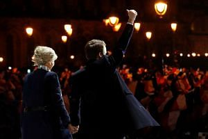 French President-elect Emmanuel Macron and his wife Brigitte Trogneux celebrating at his victory rally near the Louvre in Paris.