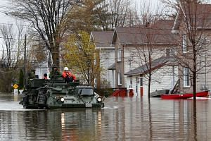 Canadian soldiers inspecting a flooded residential area in Gatineau, Quebec, Canada.
