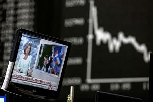 A television news report shows France's president-elect Emmanuel Macron as the DAX index curve is displayed beyond inside the Frankfurt Stock Exchange in Frankfurt, Germany, on May 8, 2017.