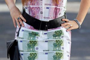 A woman wears a home-made dress featuring imitation 100 and 500 euro notes as she walks in Bordeaux, southwestern France, on Nov 7, 2014.