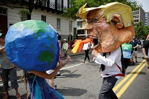 Protesters dressed as the earth and US President Donald Trump near the White House in Washington during the Peoples Climate March.