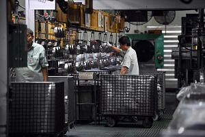 Workers at Panasonic's refrigerator compressor factory in Bedok. The Japanese company moved its refrigeration unit here to more effectively meet growing demand in Asia and streamline decision-making. The Singapore unit will also move towards becoming