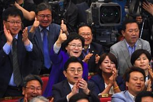 South Korea's Democratic Party members react as they watch TV screens showing the result of exit polls of the presidential election at a hall of the National Assembly in Seoul on May 9, 2017.