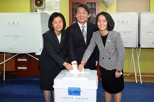Ahn Cheol Soo (centre), presidential candidate of the centre-left People's Party, his wife Kim Mi Kyung (left) and their daughter Ahn Seol Hee cast their ballots at a polling station in northern Seoul.