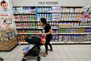 Rows of baby formula milk powder tins at a supermarket in Singapore.