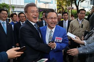 Presidential candidate Moon Jae In of the liberal Democratic Party of Korea (centre-left) hugs comic actor and his impersonator Kim Min Kyo (centre-right) during an election campaign in Seongnam, South Korea, on April 27, 2017.