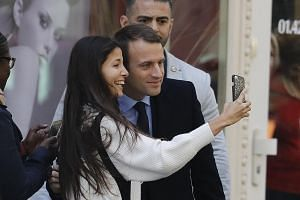 Mr Emmanuel Macron in a selfie moment with a delighted supporter after he defeated Ms Marine Le Pen in Sunday's French presidential election.