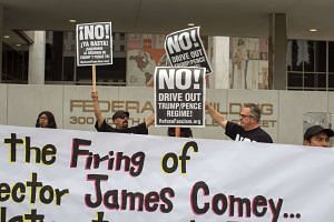Protesters, outside a federal building in Los Angeles, denouncing the firing of FBI Director James Comey.