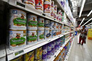 Rows of baby formula powder tins at FairPrice Xtra supermarket.