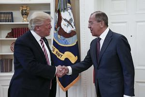 A handout photo made available by the Russian Foreign Ministry shows Trump (left) shaking hands with Lavrov.