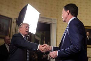 President Donald Trump (left) and former FBI Director James Comey shaking hands during a reception at the White House in Washington, US on Jan 22, 2017.