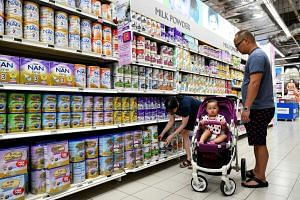 Customers looking for milk powder at a supermarket.