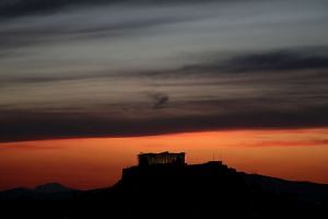 The ancient Parthenon temple is illuminated during sunset atop the Acropolis hill in Athens.