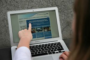 A woman points to an online British health service notice, telling users about a problem in its network.