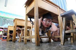 Children crouching under the tables in a classroom during a safety drill at The Third Experimental Primary School in Wen County in China's central Henan province yesterday, on the ninth anniversary of the 2008 Sichuan earthquake. The 8.0-magnitude qu