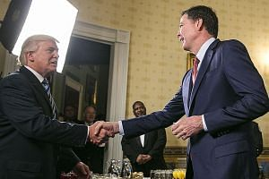 US President Donald Trump (left) and then FBI director James Comey meeting at a White House reception in January.