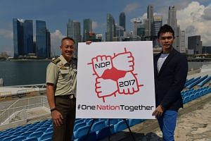 Chairman of NDP 2017 executive committee Colonel Melvin Ong (left) and 2017 theme song lyricist and singer Jay Lim with the 2017 NDP logo.