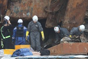 A search team examining the wreck of the Sewol, in the port of Mokpo, South Korea, on May 13, 2017.
