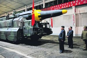 North Korean leader Kim Jong Un (centre) views a missile after the country test-fired a ballistic rocket on May 14, 2017.