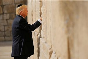 US President Donald Trump placing what seemed to be a written prayer or note between the stones of the Western Wall, the holiest site where Jews can pray, in Jerusalem's Old City yesterday. He made history by becoming the first sitting US president t