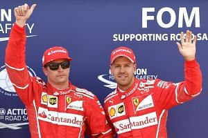 Ferrari's Finnish driver Kimi Raikkonen (left) celebrates after winning the pole position next to second placed Ferrari's German driver Sebastian Vettel.
