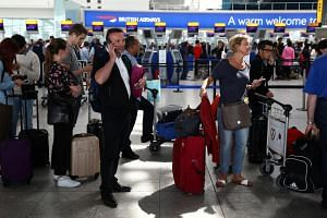 People wait with their luggage at the British Airways check-in desks at Heathrow Terminal 5 in London on May 28.