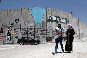A Palestinian family walking past Israel's controversial barrier in the West Bank city of Bethlehem. The Six Day War overhauled not only the annals of military strategy - it also transformed the Middle East beyond recognition and unleashed a series o