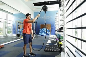 Joseph Schooling using the rope resistance trainer in the new sports gym at the Chinese Swimming Club last November, when he was the guest of honour at the official opening of the gym. He views the Budapest world meet as a chance to erase bitter memo