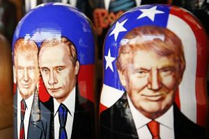 Traditional Russian Matryoshka wooden dolls also known as nesting dolls, illustrated with the images of US President Donald J. Trump and Russian President Vladimir Putin.