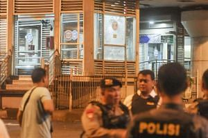 Indonesian police officers securing the area where two explosions occurred near Terminal Kampung Melayu in Jakarta, Indonesia, on May 24, 2017. At least two people, including a suspected suicide bomber, were killed. PHOTO: IWAN HIDAYAT