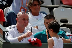 Agassi watches during Djokovic's second-round match against Portugal's Joao Sousa.