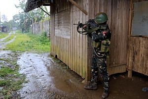 A government soldier yesterday securing an area where residents are said to be trapped in their homes as troops continue their assault on Maute insurgents, who are still holding parts of Marawi City.