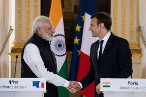 French President Emmanuel Macron (right) and Indian Prime Minister Narendra Modi, shake hands at the end of a joint statement after their meeting at the Elysee Palace in Paris, France, on June 3, 2017.