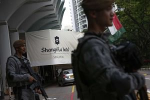 Armed police security personnel stand guard at the front of the Shangri-La Hotel, on June 2, 2017.