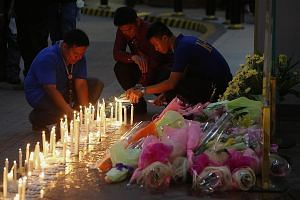 People lighting candles at the entrance of the Resorts World Manila hotel and casino complex to pay respects to victims of the attack. An investigator said in a radio interview that the gunman was likely a Filipino, contrary to previous reports that