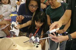 Rachelle Nathalie Mouret, eight, trying the grasper, a device used in the treatment of cancer, with her mother Daphnie Mouret, 43, at the Community Health Fair at Compass One yesterday. The fair is organised by Sengkang Health to raise awareness abou