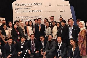 Mr Ong Ye Kung (at centre) with participants of the Southeast Asian Young Leaders' Programme at the IISS Shangri-La Dialogue yesterday. He hopes Asean states can work together to prepare the next generation for the future and exchange ideas on how to