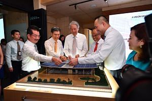 (From left) Mr Chia Ngiang Hong, CDL Group General Manager; Mr Edwin Khew, Chairman of Sustainable Energy Association of Singapore; DPM Teo; Minister Masagos; and  Mr Sherman Kwek, Deputy Chief Executive Officer, CDL, placing a piece of the solar pan