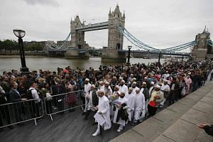 Members of the Dawoodi Bohra Muslim community (in white) joining others as they bow their heads during a vigil at Potters Fields Park in London, on June 5, 2017.