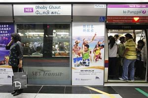 Commuters getting into a train at the Dhoby Ghaut MRT station on the North-East Line.