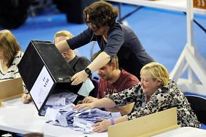 Staff members emptying a ballot box at the main Glasgow counting centre in Emirates Arena in Glasgow, Scotland, on June 8, 2017.