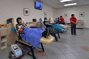 People donating blood at Bloodbank@HSA in Outram Road.