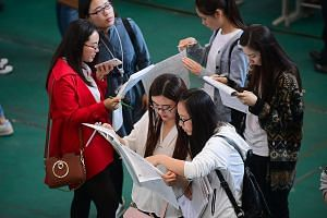 Students looking at job postings at a job fair at Shenyang Aerospace University in Shenyang, China's north-east Liaoning province, last month. More than three-quarters of recent graduates said they experienced discrimination of some form, with employ